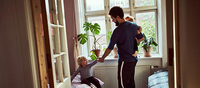 Isä ja kaksi lasta olohuoneessa.