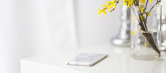 A table, which has a smart phone and a flower on it