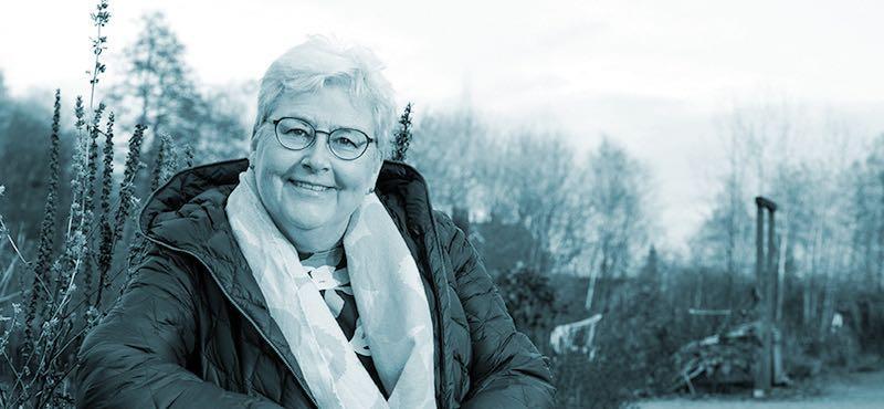 Anne Viita istumassa hymyillen puistossa penkillä.