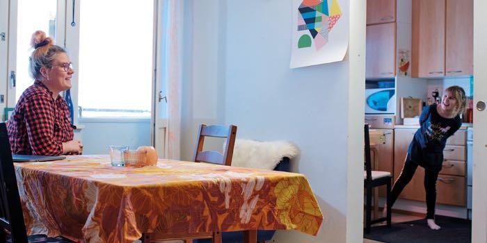 Äiti istuu ruokapöydän äärellä ja tytär kurkkaa keittiön puolelta hymyillen äitiään.
