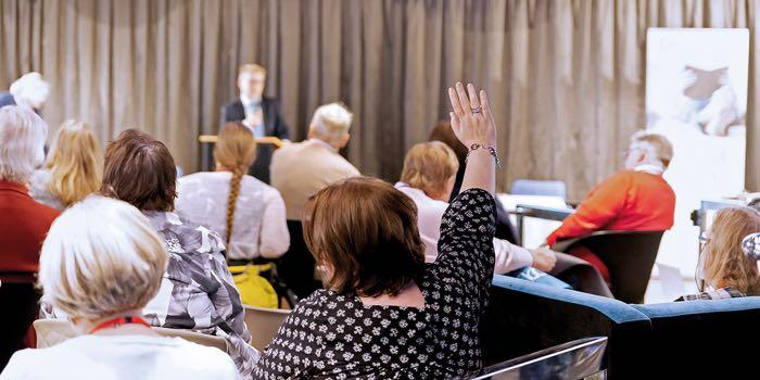 Seminaariaula, jossa on lavalla esiintyjä ja yksi yleisössä oleva osallistuja viittaamassa saadakseen suunvuoron.
