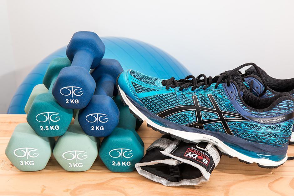 Käsipainoja kasassa ja turkoosi lenkkitossu niiden päällä, taustalla jumppapallo.