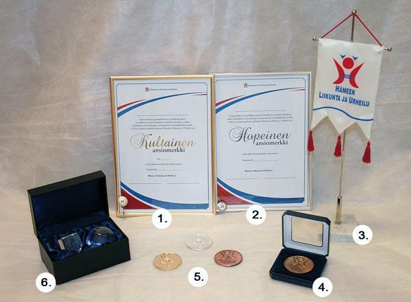 Kuvassa HLU:n kultainen- ja hopeinen ansiomerkki sekä niihin liittyvät kunniakirjat, standaari, tunnuslevyke. Lisäksi esillä HLU:n mitali sekä lasinen muistolahja, joita seurat voivat ostaan käyttöönsä.