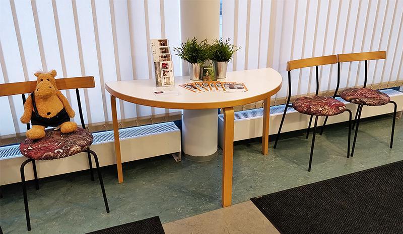 Pienperheyhdistyksen maskotti Järjestö-Heikki istuu Herttoniemen uusien tilojen aulassa.