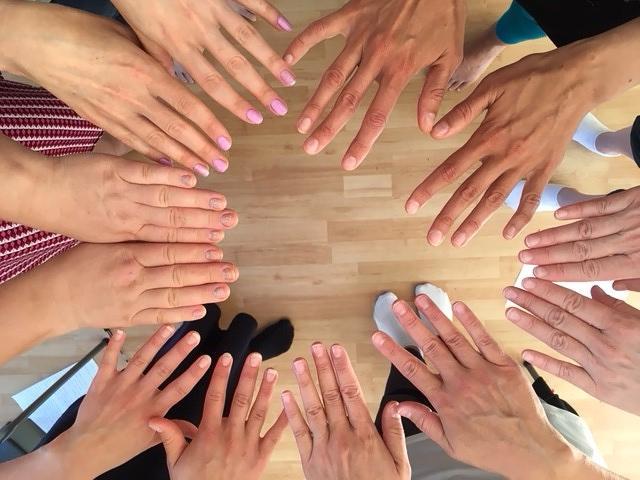 Toimintaan osallistujien kädet yhdessä ympyränmuodossa.