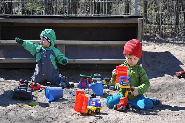 Lapset leikkivät hiekkalaatikolla.