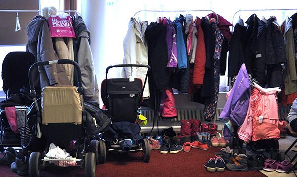 Vaatteita, kenkiä ja vaunut Pienperheyhdistyksen tiloissa.