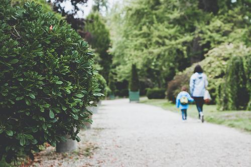 Äiti kävelee puistossa lapsensa kanssa.