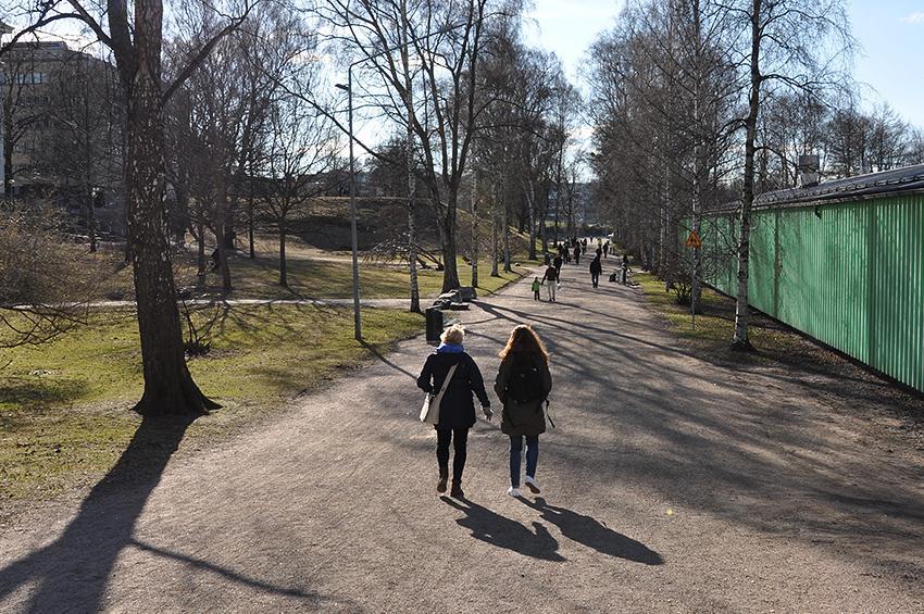 Ihmisiä kävelee puistossa.