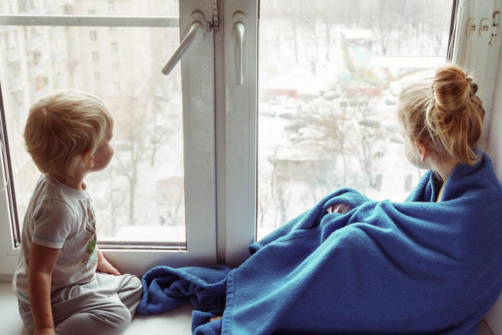 Lapset istuvat ikkunalaudalla ja katselevat ulos.