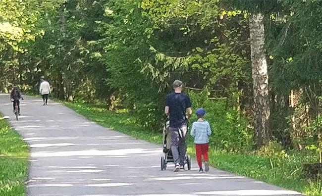 Kuvituskuva - kävelytiellä kulkee ihmisiä, mm. isä ja lapsi