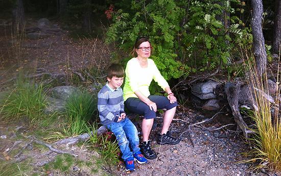 Lapsi ja Mummilan mummi istuvat puun päällä metsäretkellä.