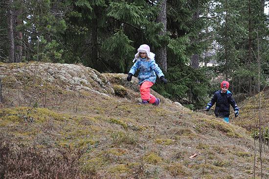 Tyttö ja poika  juoksevat ulkona, kalliolla.