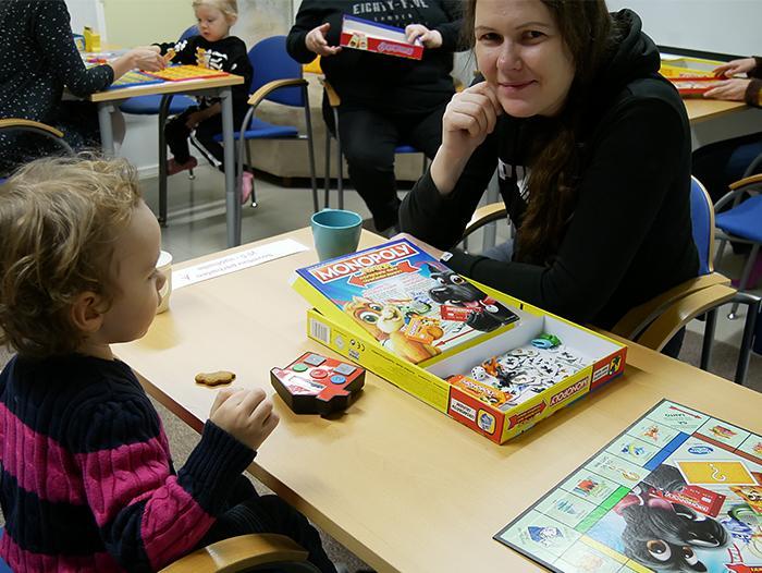 Lapsi ja äiti pelaavat lautapeliä.