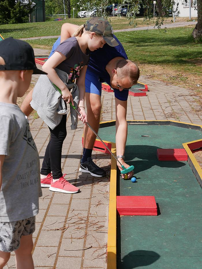 Children and male buddies are playing miniature golf.