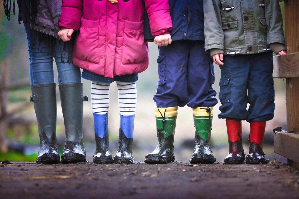 Lapset seisovat pihalla käsi kädessä.