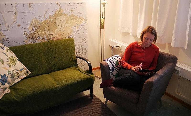 Nainen käyttää kännykkää tunnelmallisessa huoneessa.