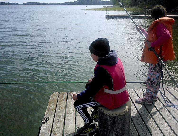 Kaksi nuorta laiturilla kalastamassa.