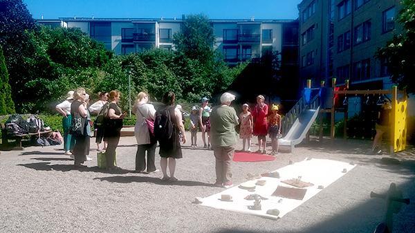 Lapset, vanhemmat ja kurssin vetäjät kokoontuneena sisäpihalle Herttoniemessä.