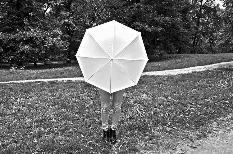 Ihminen sateenvarjon takana.