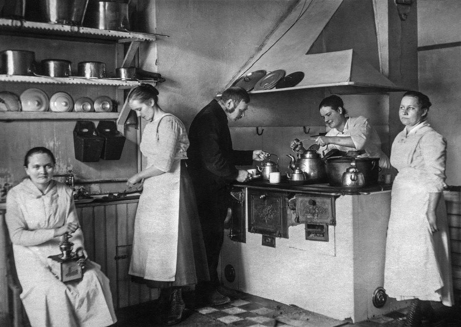 """Kuvassa Rovaniemen yleisen sairaalan keittiö vuonna 1922. Kahvimyllyä pyörittää Lyydia Jauhka. Keskellä on Iikka Paavalniemi ja oikealla Briitta Vilhelmiina """"Miina"""" Mölläri. Kuva: Iikka Paavalniemi, 1910-luku. Lapin maakuntamuseon kokoelmat."""