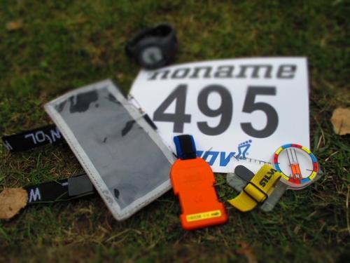 Kilpailuissa tarpeelliset varusteet: numerolappu, hakaneuloja, rastimääritekotelo, kompassi ja emit-kortti. Kuva: I-M Vaara.
