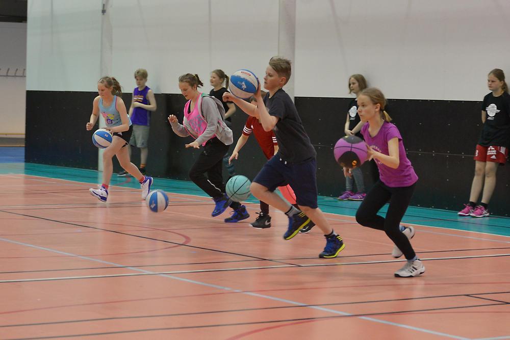 Nuoria pelaamassa koripalloa.