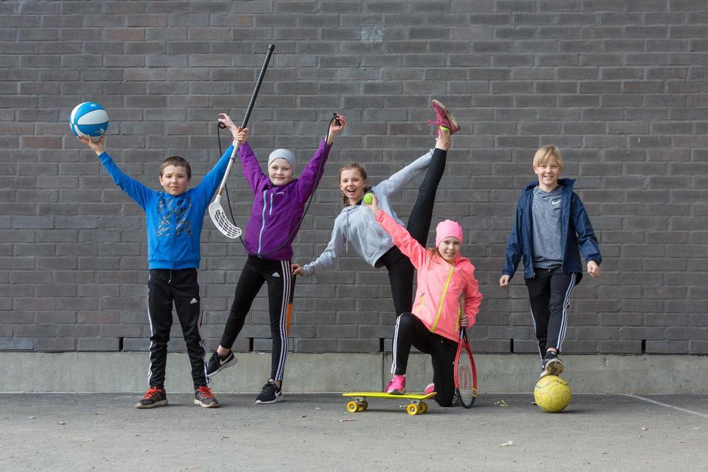 Nuoria poseeraamassa liikuntavälineiden kanssa.