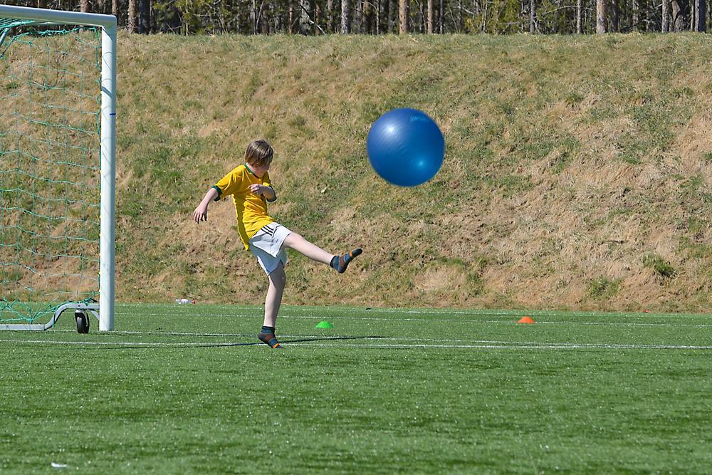 Poika potkaisemassa jumppapalloa.