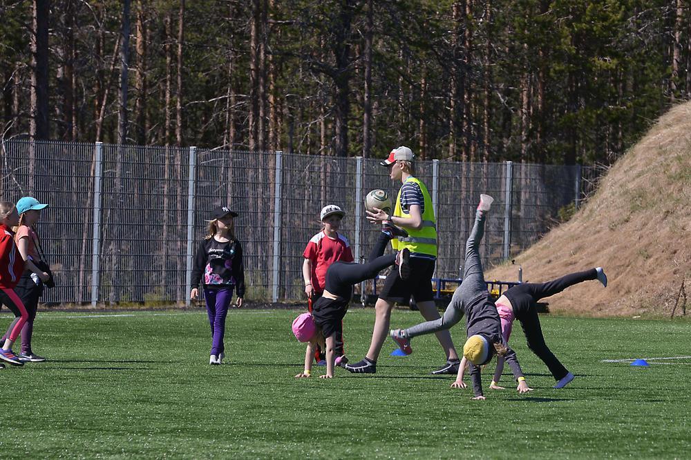 Tyttöjä tekemässä kärrynpyöriä kesken jalkapallopelin.