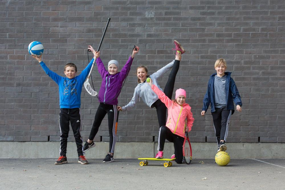 Koululaisia poseeraamassa liikuntavälineiden kanssa.