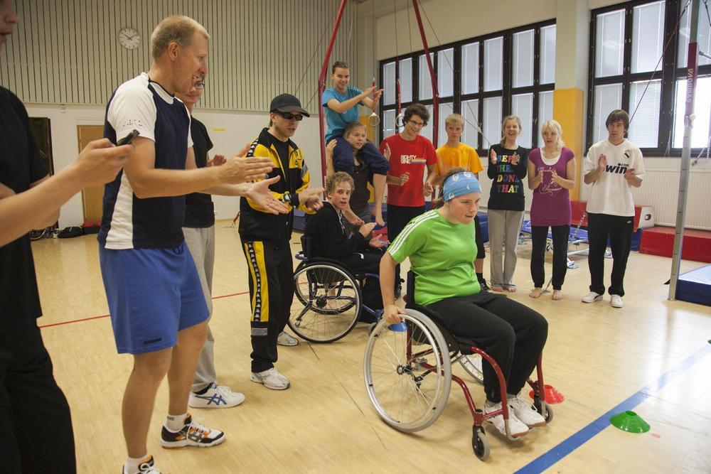 Liikkujia kannustamassa naista pyörätuolissa.