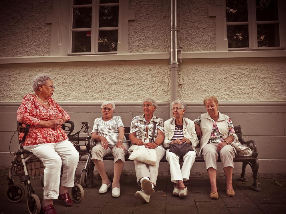 Neljä iäkästä naista juttelevat ja istuvat ulkona penkillä ja yksi nainen istuu rollaattorin päällä.