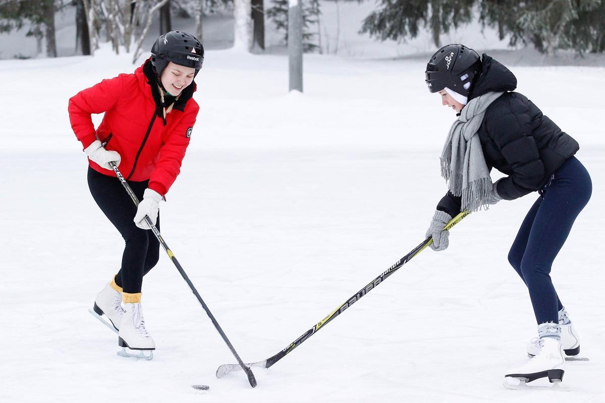 Kaksi oppilasta pelaa jääkiekkoa.
