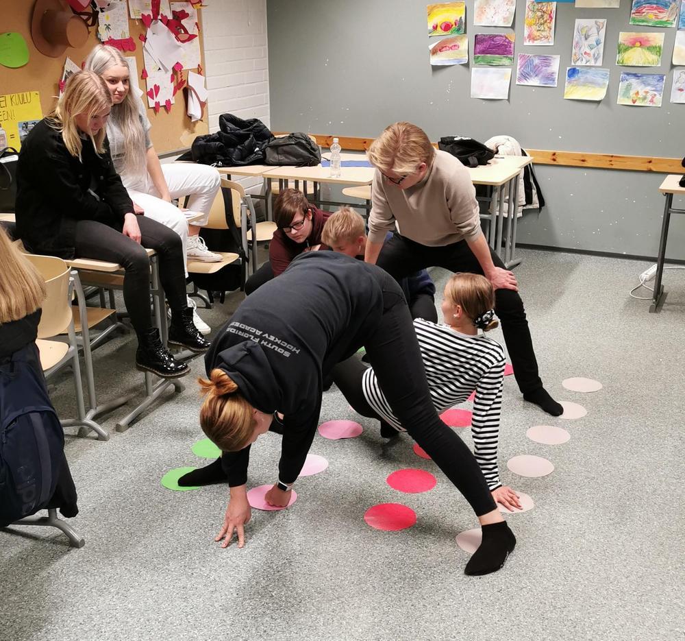 Oppilaat pelaavat Twister peliä.