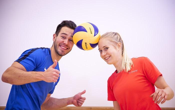 Mies ja nainen pitävät palloa pään välissä.