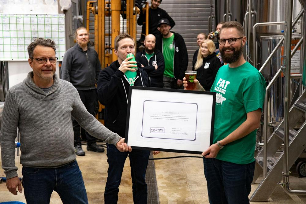 Kuvassa Reilu vero ry:n puheenjohtaja Kim Remitz luovuttaa Reilu vero -sertifikaatin Fat Lizard Brewing Companyn edustajille panimon tiloissa Espoossa.