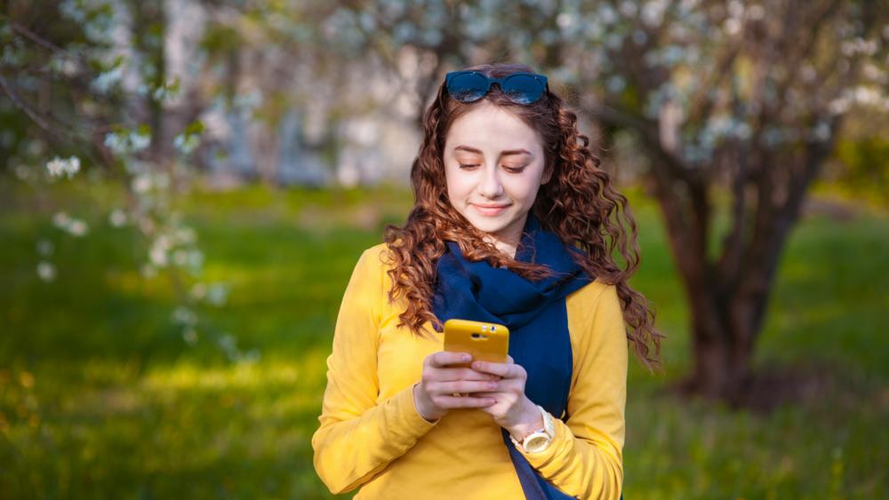 Nuori nainen oranssissa paidassa pitää käsissään puhelinta ja katsoo sen näyttöä.