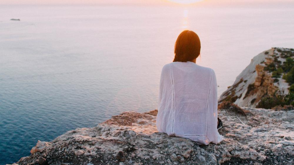 Nainen valkoisessa neuleessa istuu kalliolla kasvot vesistöön päin