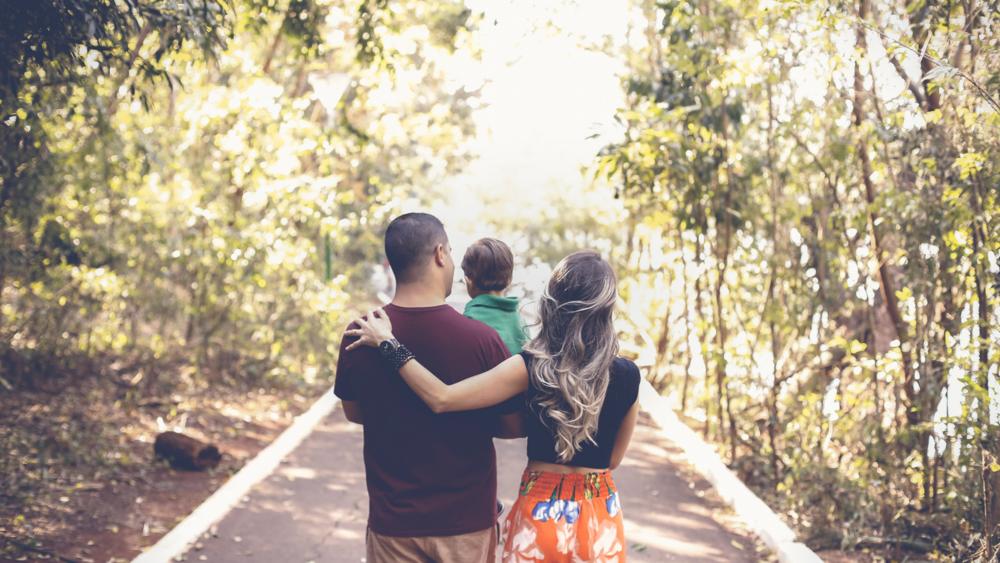 Nainen ja mies, jotka pitävät lasta sylissä välissään. Selät katsojaan päin, katsovat eteenpäin tietä, jonka reunoilla tiheästi puita.