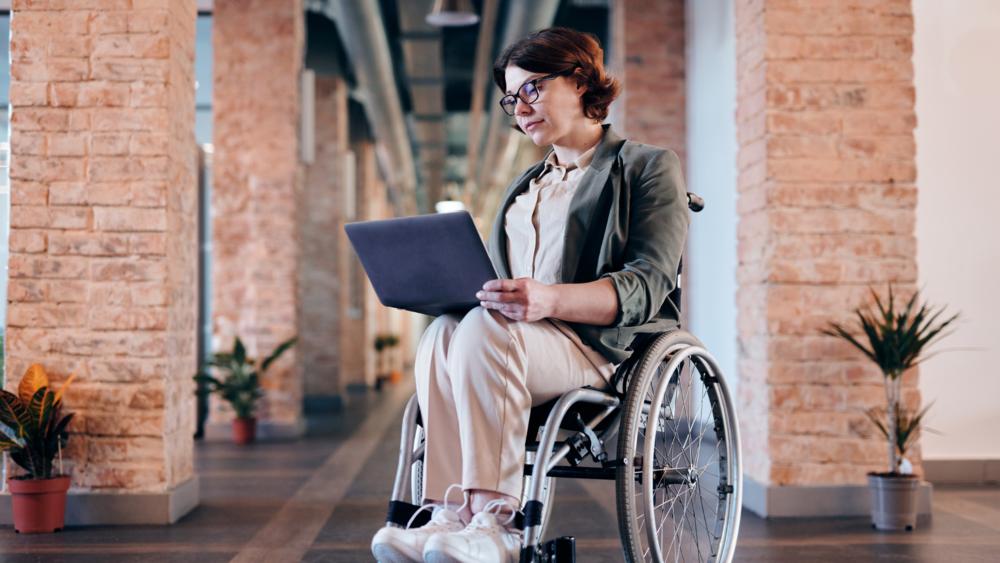 Nainen istuu pyörätuolissa, sylissä kannettava tietokone, jonka näyttöä nainen katsoo.