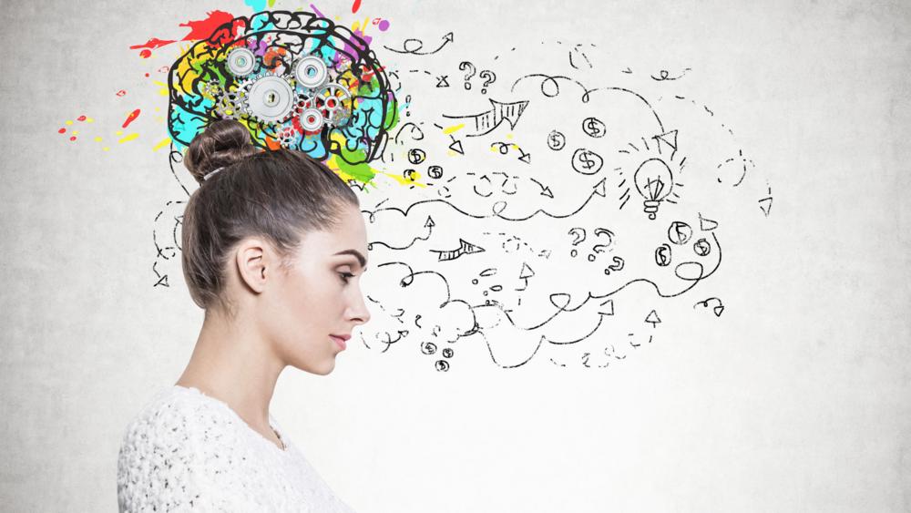 Nainen, jonka takana vaalealla seinällä värikäs aivojen kuva.