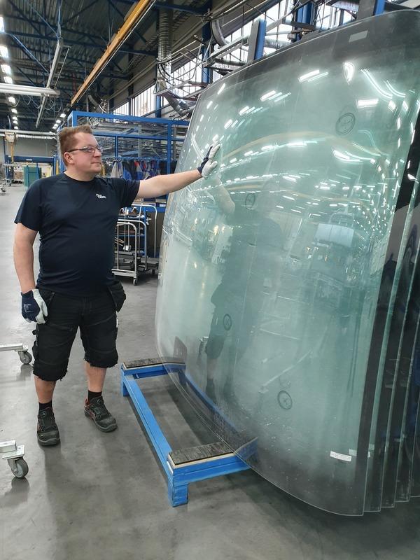Mies esittelemässä bussin tuulilasia tehtaalla.