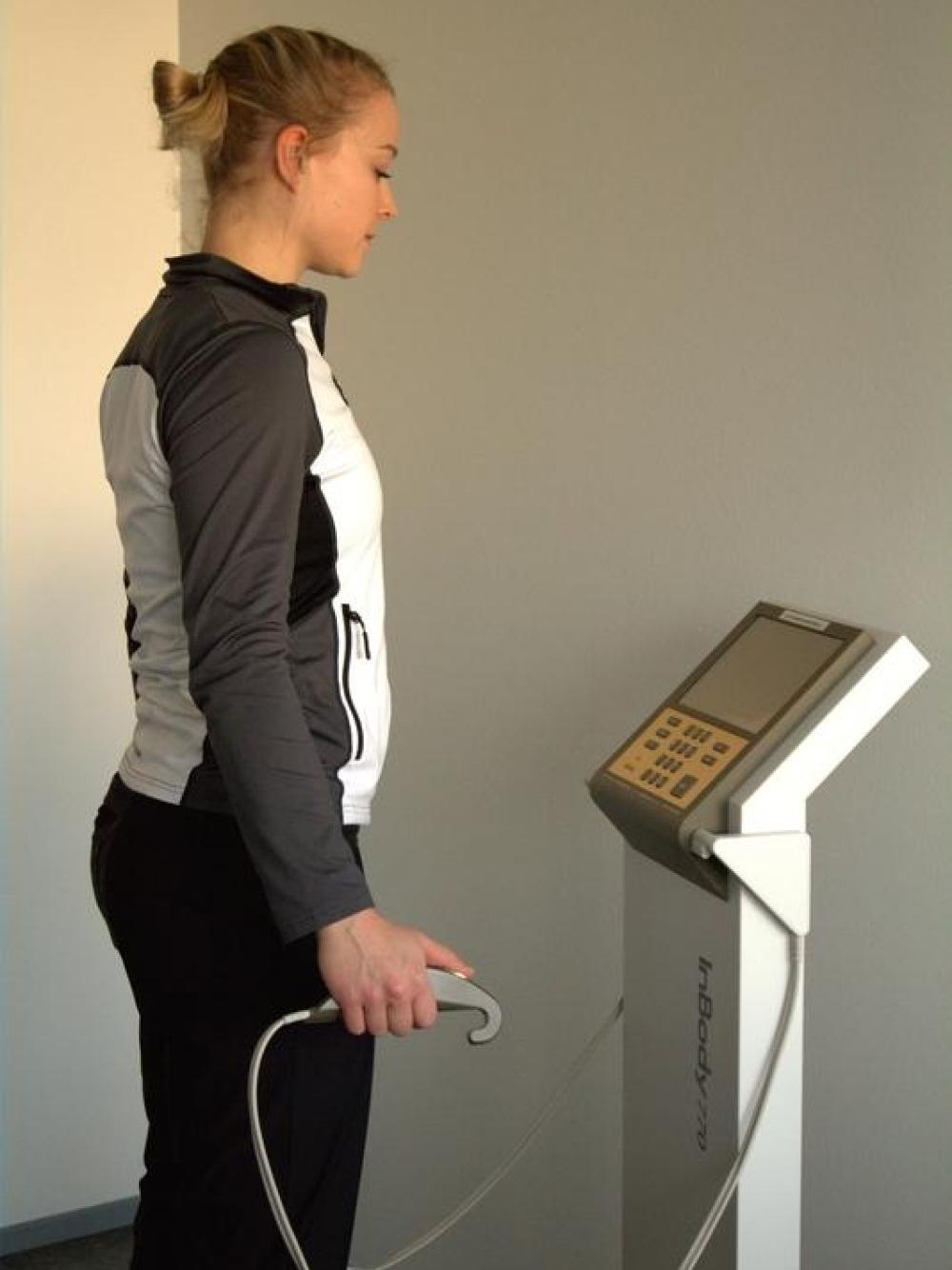 Nainen testaamassa kehonkoostumusta.