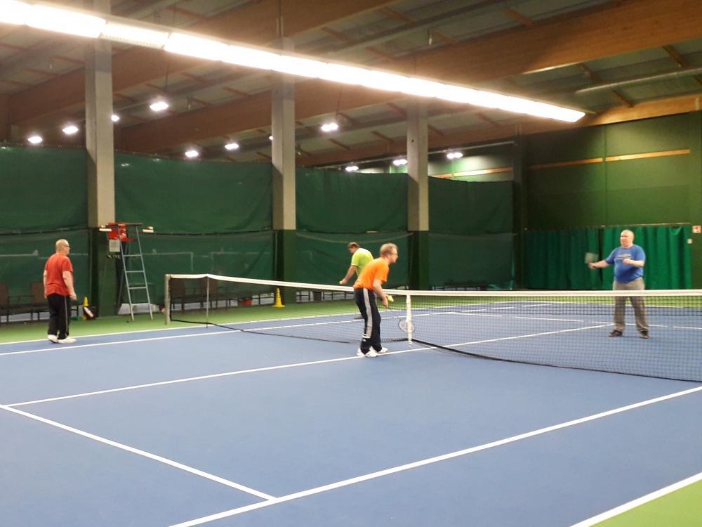 Aikuisia pelaamassa tennistä.