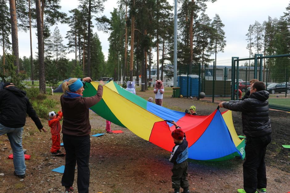 Lapset ja aikuiset pelaamassa ryhmäpeliä.