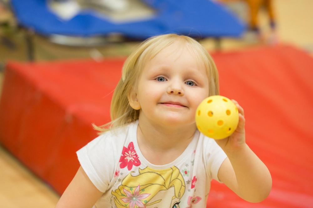 Tyttö sählypallo kädessä.