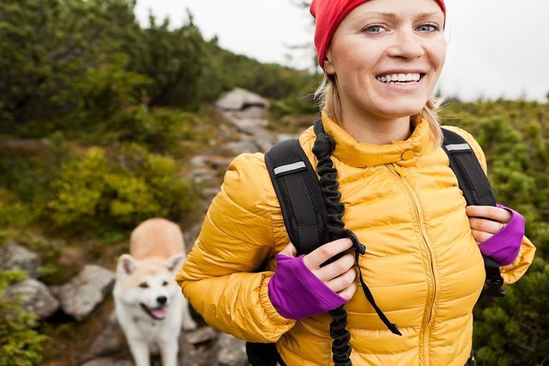Nainen ulkoilemassa koiran kanssa.