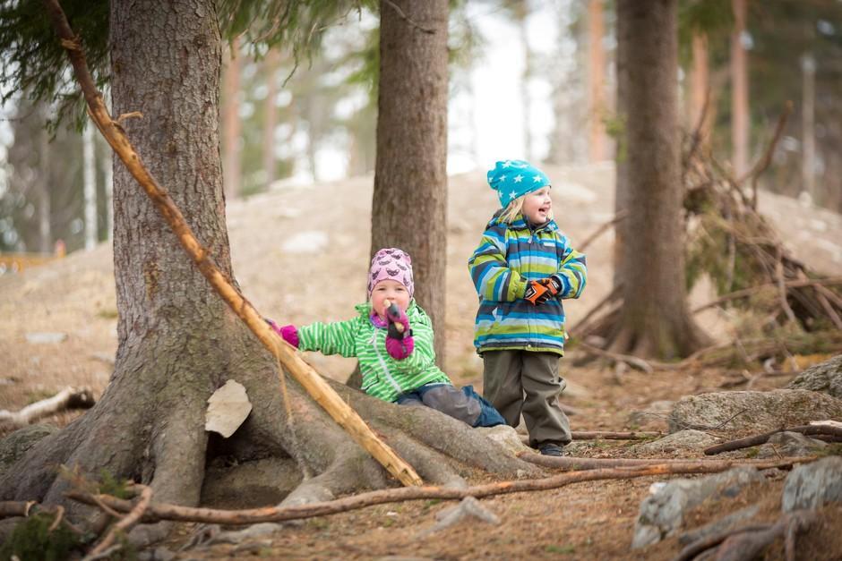 Nuoria leikkimässä metsässä.