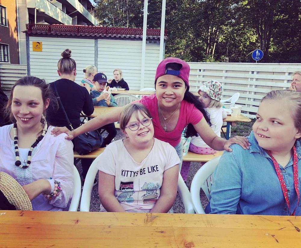 Kuvassa neljä tyttöä istuvat pöydän ääressä vierekkäin ja hymyilevät kameralle.